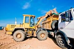 倾销者装入程序装料机卡车轮子 免版税库存图片