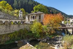假定、河和秋天树的19世纪教会在Shiroka Laka,保加利亚镇  免版税库存照片