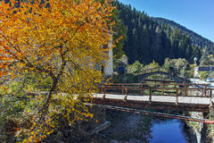 假定、河和秋天树的19世纪教会在Shiroka Laka,保加利亚镇  图库摄影