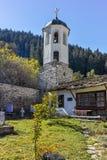 假定、河和秋天树的19世纪教会在Shiroka Laka,保加利亚镇  免版税图库摄影