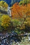 假定、河和秋天树的19世纪教会在Shiroka Laka,保加利亚镇  免版税库存图片