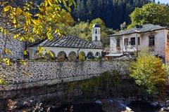 假定、河和秋天树的19世纪教会在Shiroka Laka,保加利亚镇  库存图片