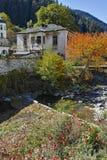 假定、河和秋天树的19世纪教会在Shiroka Laka,保加利亚镇  库存照片