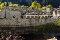 假定的19世纪教会的秋天视图在Shiroka Laka,保加利亚镇  免版税库存图片