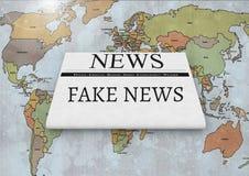 假新闻在世界地图的报纸发短信 库存照片