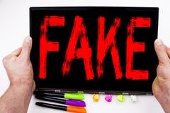 假新闻在有标志的,笔,文具办公室发短信写在片剂,计算机 假新闻白色backgr的企业概念 免版税库存照片