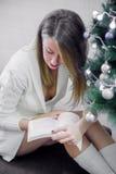 假日、休闲、文学和人概念阅读书和开会在长沙发在圣诞树在家点燃背景 免版税库存照片