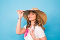 假日、夏天、时尚和人概念-流行的服装草帽的女孩 迷人的妇女画象蓝色的 库存照片