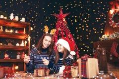 假日、家庭和人概念 愉快的母亲和女孩圣诞老人帮手帽子的有闪烁发光物的在手上,礼物 库存照片
