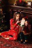 假日、庆祝和人概念-年轻女人深色的卷发,穿戴在圣诞节内部b的圣诞节衣服 图库摄影