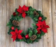 假日一品红在土气木板的圣诞节花圈 库存照片
