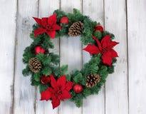 假日一品红在土气白色木板的圣诞节花圈 免版税库存图片