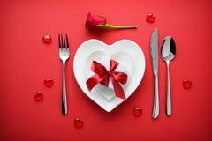 假日与一个礼物盒的桌设置在红色背景 免版税库存图片