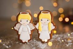 假日传统食物面包店 姜饼对在舒适温暖的装饰的小的逗人喜爱的天使男孩和女孩与诗歌选光 免版税库存图片