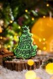 假日传统食物面包店 姜饼绿色在舒适温暖的装饰的圣诞树与诗歌选光 免版税图库摄影