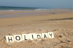 假日信件在一个晴朗的海滩的与海在背景中 库存照片
