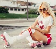 假日和假期 城市公园方式 葡萄酒溜冰鞋的,太阳镜, T恤杉s一名观看者腿长的长发年轻白肤金发的妇女 库存照片