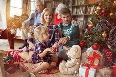 假日和庆祝概念-幸福家庭装饰一棵圣诞树 免版税图库摄影