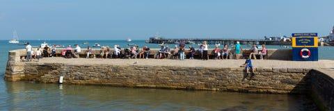 假日和访客港口的围住Swanage等待的小船旅行全景 免版税库存图片