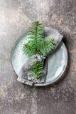 假日圣诞节食物背景、利器、板材、餐巾与圆环和圣诞树分支,制表设置在银 免版税图库摄影