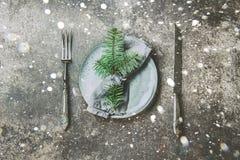 假日圣诞节食物背景、利器、板材、餐巾与圆环和圣诞树分支,制表设置在银 图库摄影