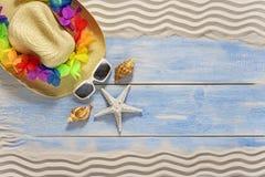 假日在海边,夏天,在海滩木地板上的帽子 免版税库存图片