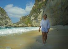 假日她的50s的与灰色头发走在热带天堂沙漠的愉快和轻松的亚裔成熟妇女生活方式画象  免版税图库摄影