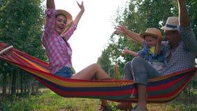 假日家,有孩子的愉快的父母吊床的在苹果庭院获得乐趣和享用自然在草帽在温暖 股票视频