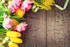 假日春天背景 照顾用五颜六色的郁金香花和含羞草花装饰的` s天假日木背景框架 免版税库存照片