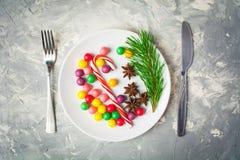 假日服务概念用在板材和扁平的餐具的糖果 库存图片