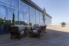 假日桌、椅子、一个沙发和闭合的伞在门廊 免版税库存图片