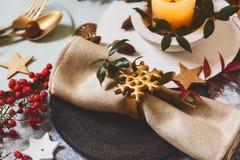 假日桌设置,有金黄餐巾持有人的黑色的盘子与星形状,在土气纹理,围拢由装饰品nandine 免版税图库摄影