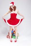 假日概念和想法 有被举的礼服的愉快的微笑的白种人红发圣诞老人帮手 后边礼物Penty  库存照片