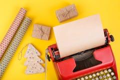 假日概念-有空白的工艺纸、礼物盒和包装纸的打字机在黄色背景 免版税图库摄影