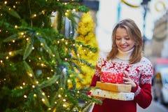 假日毛线衣的愉快的少女有堆的圣诞礼物 免版税库存照片