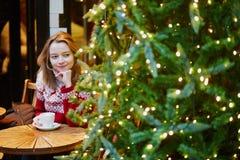 假日毛线衣饮用的咖啡或巧克力热饮的女孩在为圣诞节装饰的咖啡馆 库存照片