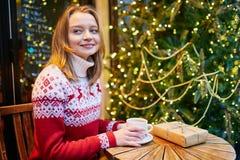 假日毛线衣饮用的咖啡或巧克力热饮的女孩在为圣诞节装饰的咖啡馆 免版税库存图片