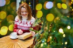 假日毛线衣饮用的咖啡或巧克力热饮的女孩在为圣诞节装饰的咖啡馆 库存图片