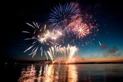 假日烟花水面上与在黑天空背景的反射 免版税库存照片