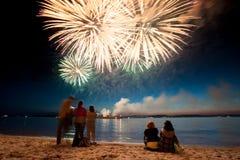 假日烟花水面上与在黑天空背景的反射 免版税库存图片