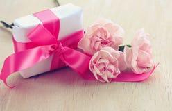 假日背景,白色礼物盒,三支桃红色康乃馨 库存照片