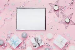 假日装饰、框架和礼物盒在时髦的桃红色台式视图 时尚圣诞节背景 平的位置 党大模型 免版税库存照片