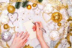假日装饰和笔记本有目标的在白色土气桌上,平的位置样式 圣诞节计划概念 免版税库存图片