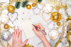 假日装饰和笔记本有目标的在白色土气桌上,平的位置样式 圣诞节计划概念 免版税图库摄影