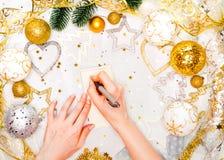 假日装饰和笔记本有目标的在白色土气桌上,平的位置样式 圣诞节计划概念 库存图片