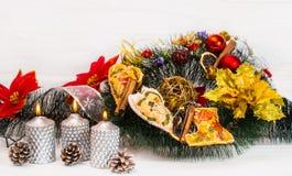 假日装饰蜡烛和一个手工制造花圈 免版税库存图片