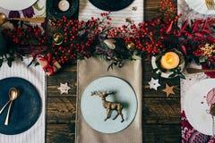 假日金餐位餐具,与装饰品的滑稽的圣诞节桌 图库摄影