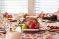 假日饭桌用烤火鸡,在前景的人倾吐的红酒 免版税图库摄影