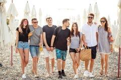 假日,假期 获得小组的朋友在海滩,走,饮料啤酒,微笑和拥抱的乐趣 图库摄影