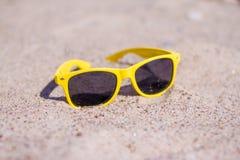 假日,在夏天放松,旅行和vacantion概念-在沙滩的黄色太阳镜 免版税图库摄影